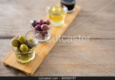 Marinated olives with olive oil and balsamic vinegar in glass container on a wooden tray stock photo, Close-up of marinated olives with olive oil and balsamic vinegar in glass container on a wooden tray by Wavebreak Media
