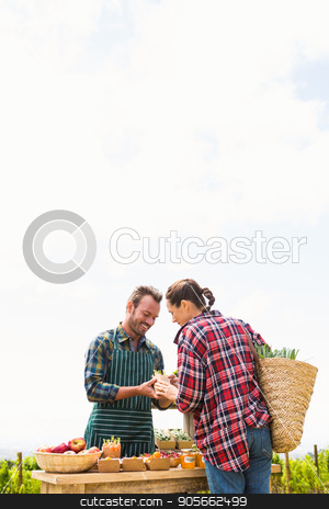 Woman buying organic vegetables from man against sky stock photo, Young woman buying organic vegetables from man against sky at farm by Wavebreak Media