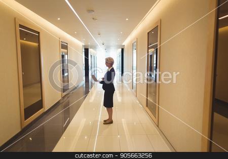 Businesswoman using laptop in corridor stock photo, Businesswoman using laptop while standing in corridor by Wavebreak Media