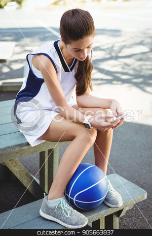 Woman using smart phone while sitting on picnic table stock photo, High angle view woman using smart phone while sitting on picnic table by Wavebreak Media
