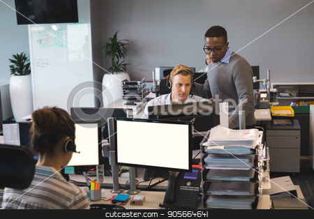 Focused young business colleagues working at office stock photo, Focused young business colleagues working at desk in office by Wavebreak Media