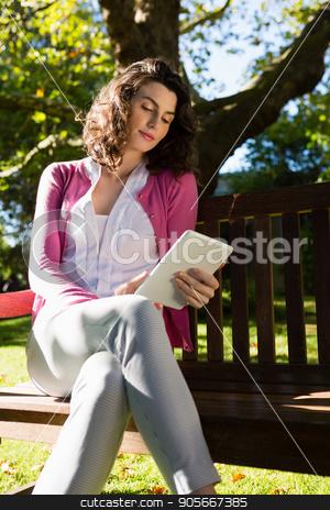 Woman sitting on bench and using digital tablet in garden stock photo, Woman sitting on bench and using digital tablet in garden on a sunny day by Wavebreak Media
