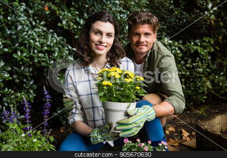 Couple holding sapling plant in garden stock photo, Portrait of smiling couple holding sapling plant in garden by Wavebreak Media