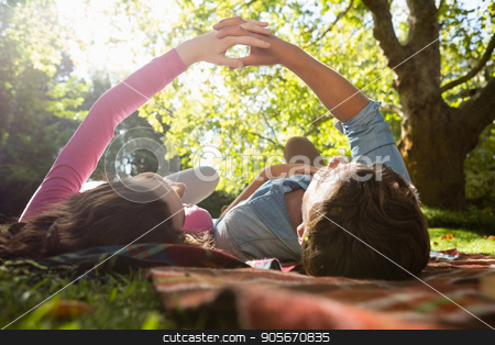 Romantic couple lying on picnic blanket in park stock photo, Romantic couple lying on picnic blanket in park on a sunny day by Wavebreak Media
