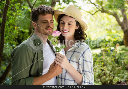 Smiling couple looking at flower in garden stock photo, Couple smelling flower in garden on a sunny day by Wavebreak Media
