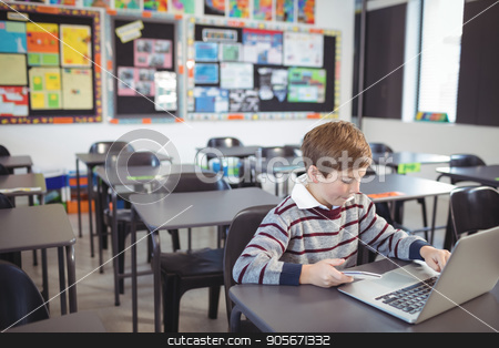 Schoolboy using laptop and mobile phone on desk stock photo, Schoolboy using laptop and mobile phone on desk at classroom by Wavebreak Media
