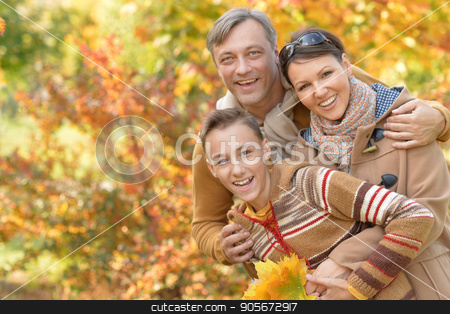 Happy family in park stock photo, Portrait of happy young family in autumn park by Ruslan Huzau