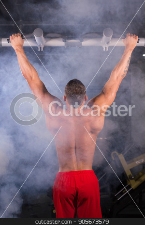 Strong man doing pull-ups on a bar in a gym. stock photo, Strong man doing pull-ups on a bar in a gym by Satura86