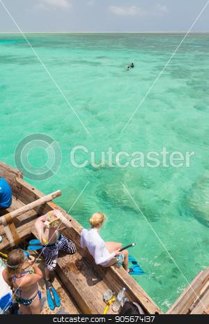 Woman snorkeling in clear shallow sea of tropical lagoon with turquoise blue water. stock photo, Woman snorkeling in clear shallow sea of tropical lagoon with turquoise blue water and coral reef, near exotic island. Mnemba island, Zanzibar, Tanzania. by kasto