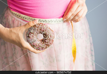 Woman holding donut in hand and check out his body fat with measuring tape. stock photo, Woman holding donut in hand and check out his body fat with measuring tape by Satura86