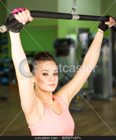 health, fitness, lifestyle, technology and people concept - Sportive young woman in a gym training. Working out in a sport club stock photo, Sportive young woman in a gym training. Working out in a fitness gym. by Satura86
