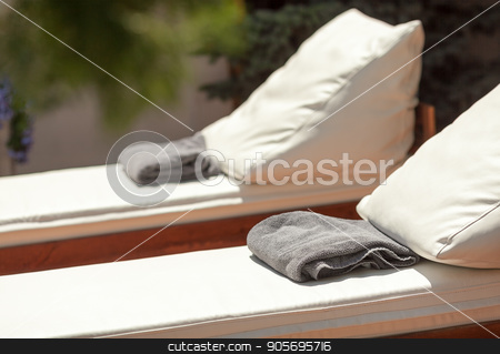 hotel rest, vacations and summer joy concept - closeup beautiful sun loungers with cushions and towels for relaxing, resort entertainments, solar spa near pool, deckchairs made of wood and leather . stock photo, hotel rest, vacations and summer joy concept - closeup beautiful sun loungers with cushions and towels for relaxing, resort entertainments, solar spa near pool, deckchairs made of wood and leather by Dmitry