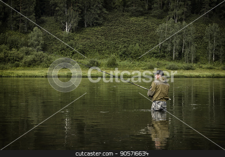 single fisherman on a calm river is autumn fishing stock photo, single fisherman on a calm river is autumn fishing. by Alexander