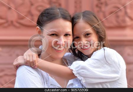 Mother hugging little daughter stock photo, Mother hugging her cute little daughter and looking at camera by Ruslan Huzau