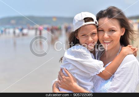 Mother hugging little daughter stock photo, Mother hugging her cute little daughter on seashore by Ruslan Huzau