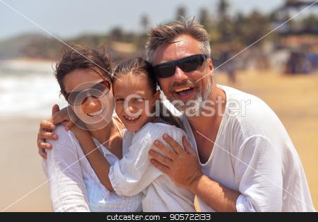 happy family hugging stock photo, Portrait of happy family hugging on seashore by Ruslan Huzau