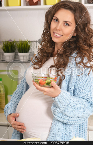pregnant woman having breakfast stock photo, Young pregnant woman having breakfast at kitchen by Ruslan Huzau
