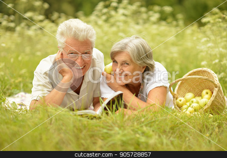 Elderly couple lying on autumnal leaves  stock photo, Elderly couple lying on fallen autumnal leaves in park and looking at camera by Ruslan Huzau