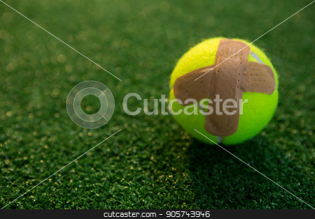 Close up of tennis ball with bandage on field stock photo, Close up of tennis ball with bandage on field by Wavebreak Media
