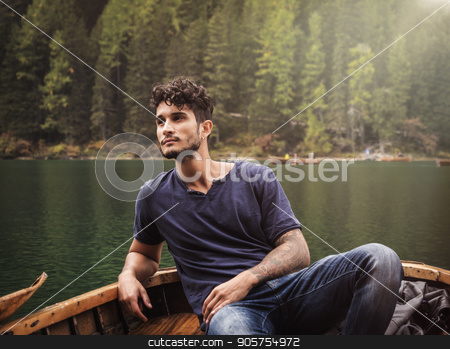 Young man relaxing in boat stock photo, Handsome tattooed man sitting in boat on background of woods on shore of lake looking away.  by Stefano Cavoretto