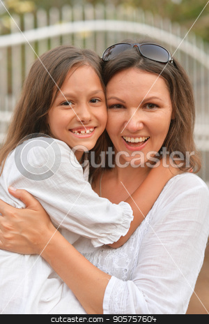 Mother hugging little daughter stock photo, Mother hugging her cute little daughter on seashore by Ruslan Huzau