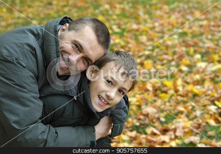 Father and son having fun  stock photo, Father and son having fun together at autumnal park by Ruslan Huzau