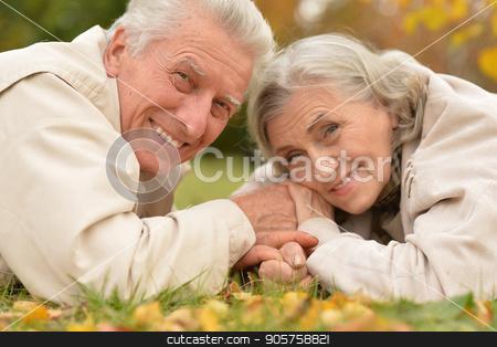 couple in autumn park lying stock photo, happy Senior couple in autumn park lying by Ruslan Huzau