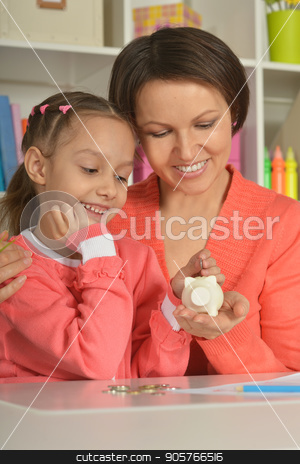 Mother and  Daughter with Piggy Bank stock photo, Mother and Child Daughter Putting Coins into Piggy Bank by Ruslan Huzau