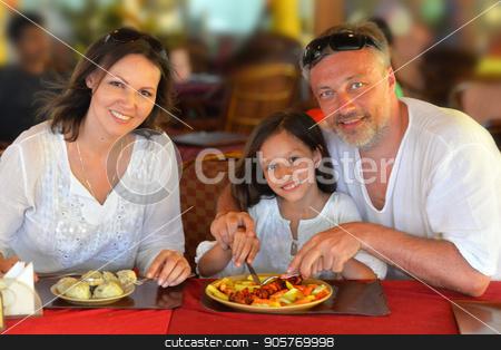 smiling family eating at cafe stock photo, Happy smiling family eating at cafe together by Ruslan Huzau