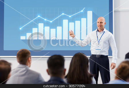 group of people at business conference or lecture stock photo, business, statistics and people concept - smiling businessman or lecturer with diagram chart on projection screen and group of students at conference presentation or lecture by Syda Productions