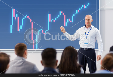 group of people at business conference or lecture stock photo, business, economy and people concept - smiling businessman or financier with forex chart on projection screen and group of students at conference presentation or lecture by Syda Productions