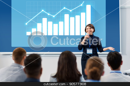 group of people at business conference or lecture stock photo, business, statistics and people concept - smiling businesswoman or lecturer with microphone and diagram chart on projection screen talking to group of students at conference presentation or lecture by Syda Productions