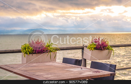 Outdoor table on lake shore stock photo, Conceptual image with an empty table, on a terrace, on the shore of the Bodensee lake, at sunset. by Daniela Simona Temneanu