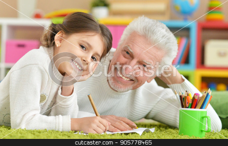 Grandfather playing with granddaughter  stock photo, Grandfather playing with granddaughter in a room by Ruslan Huzau