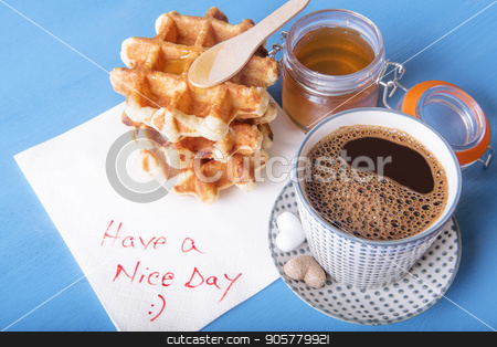 Tasty breakfast and napkin message stock photo, Cup of coffee with heart shaped sugar, homemade waffles with honey and a napkin with have a nice day message, on a blue wooden table. by Daniela Simona Temneanu