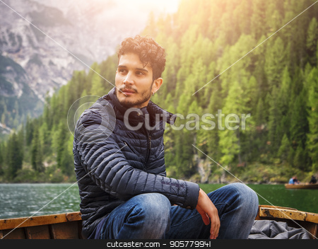 Handsome man rowing in boat stock photo, Young casual man sitting in boat and rowing while looking away on background of lake and mountains. by Stefano Cavoretto