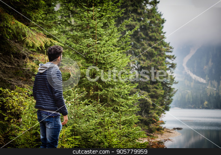 Young man relaxing in the mountain stock photo, Handsome yung man standing on background of woods on shore of lake looking away. by Stefano Cavoretto