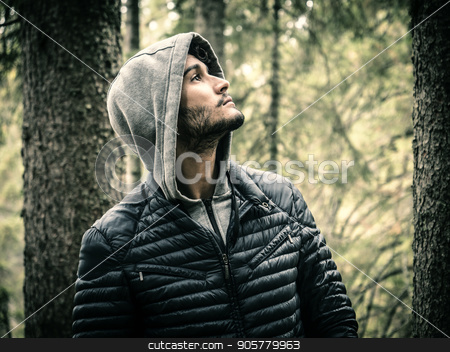 Young man relaxing in the mountain stock photo, Handsome yung man standing on background of woods looking away. by Stefano Cavoretto