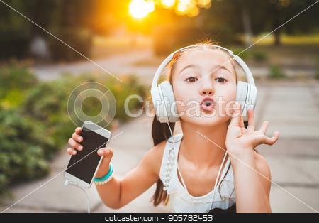 girl with headphones sending air kiss stock photo, girl with headphones sending air kiss to somebody, cute and pretty child making sweet gesture by Oleh