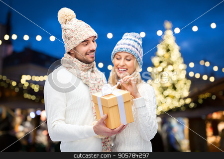 happy couple with gift box over christmas lights stock photo, holidays and people concept - happy couple in winter hats with gift box over christmas tree lights background by Syda Productions