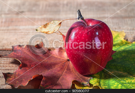 Apple and autumn leaves stock photo, Apple and autumn leaves on old wooden table by Vitalii Borovyk