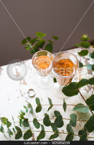 glass of rose wine stock photo, eucalyptus branches on an old table with a glass of rose wine and wedding rings by Sergiy Artsaba