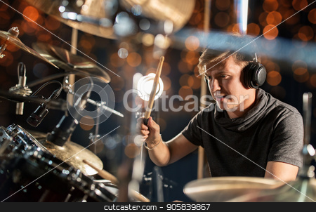 male musician playing drum kit at concert stock photo, music, people, musical instruments and entertainment concept - male musician in headphones with drumsticks playing drum kit at concert or studio over holidays lights background by Syda Productions