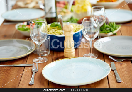 table served with plates, wine glasses and food stock photo, catering and eating concept - table served with plates, wine glasses and food by Syda Productions