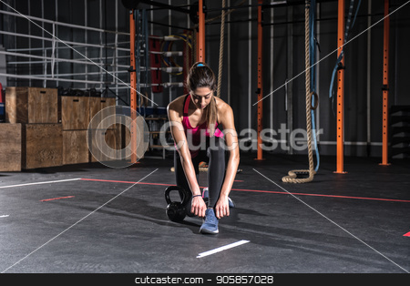Athletic girl ready to start exercises with a kettlebell at the gym stock photo, Determined athletic girl ready to start exercises with a kettlebell at the gym by Federico Caputo