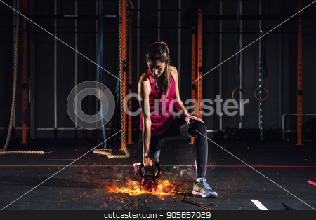 Athletic girl works out at the gym with a fiery kettlebell stock photo, Determined athletic girl works out at the gym with a fiery kettlebell by Federico Caputo