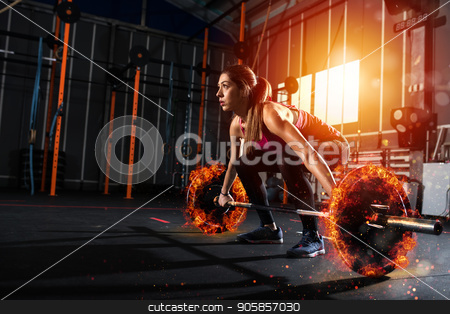 Athletic girl works out at the gym with a fiery barbell stock photo, Determined athletic girl works out at the gym with a fiery barbell by Federico Caputo