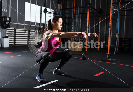 Athletic girl does squat exercises at the gym stock photo, Determined athletic girl does squat exercises at the gym by Federico Caputo