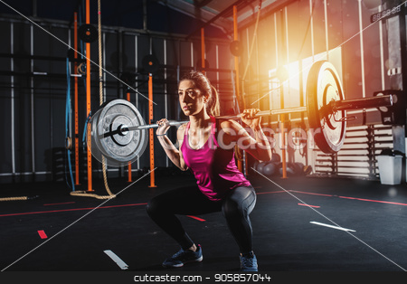 Athletic girl works out at the gym with a barbell stock photo, Determined athletic girl works out at the gym with a barbell by Federico Caputo