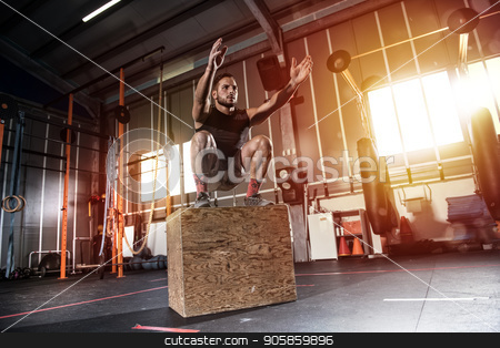 Athletic man does box jump exercises at the gym stock photo, Determined athletic man does box jump exercises at the gym by Federico Caputo